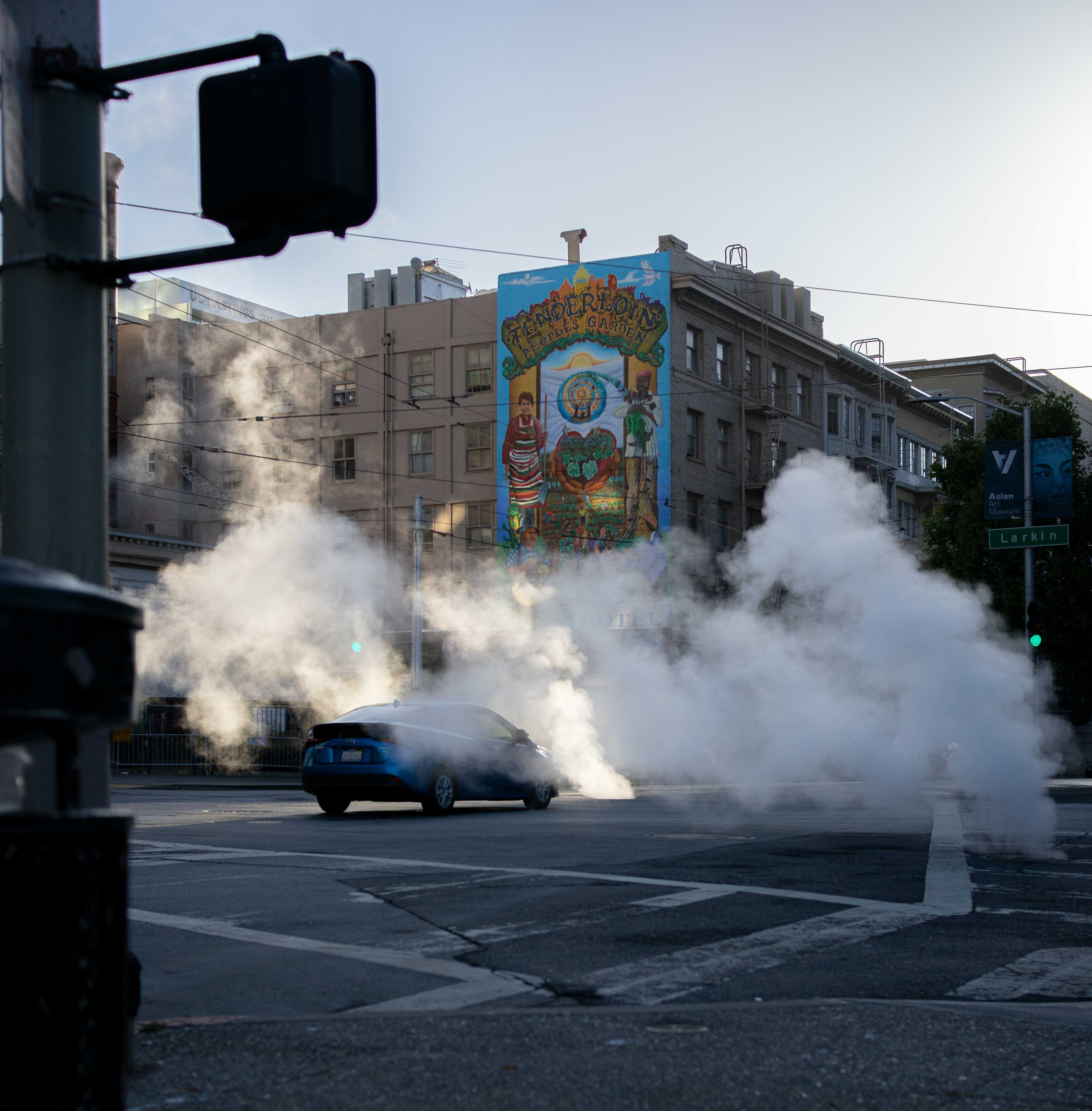 a black car surrounded by smoke in a city road