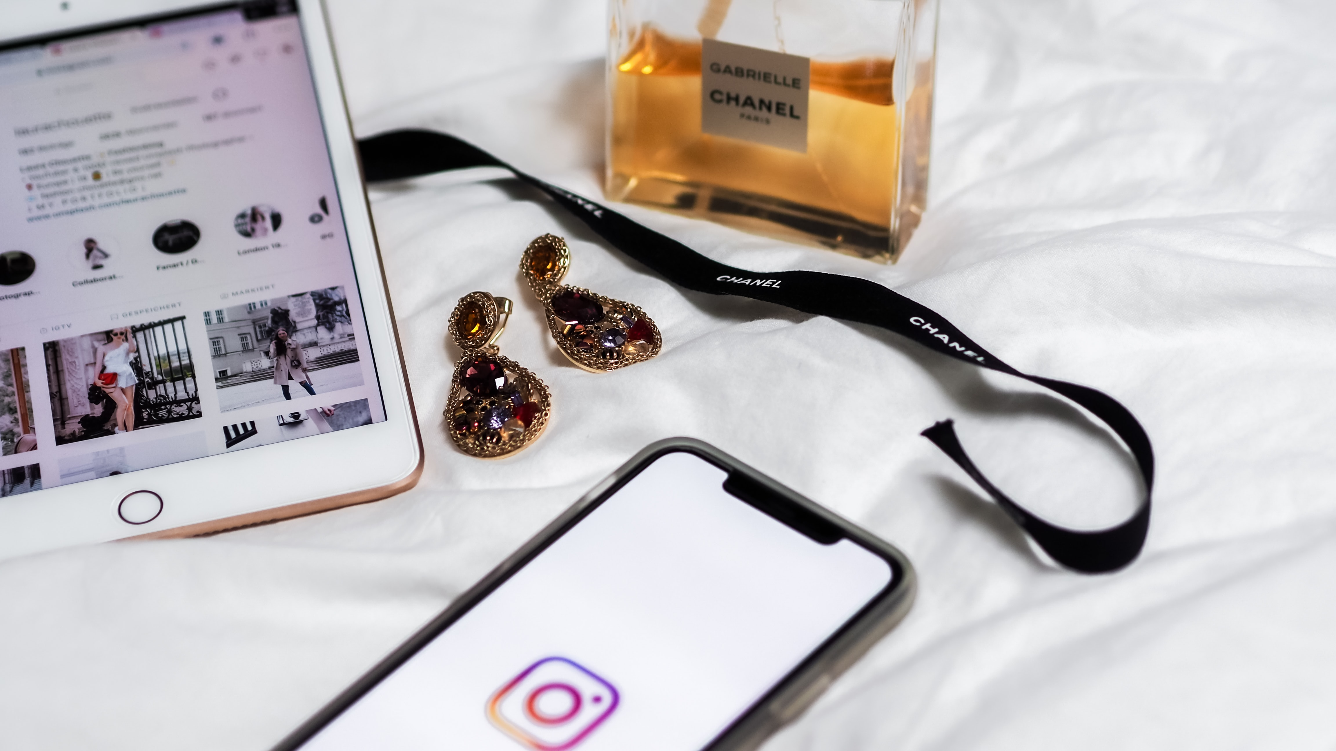 earrings and perfume next to mobile devices with white background