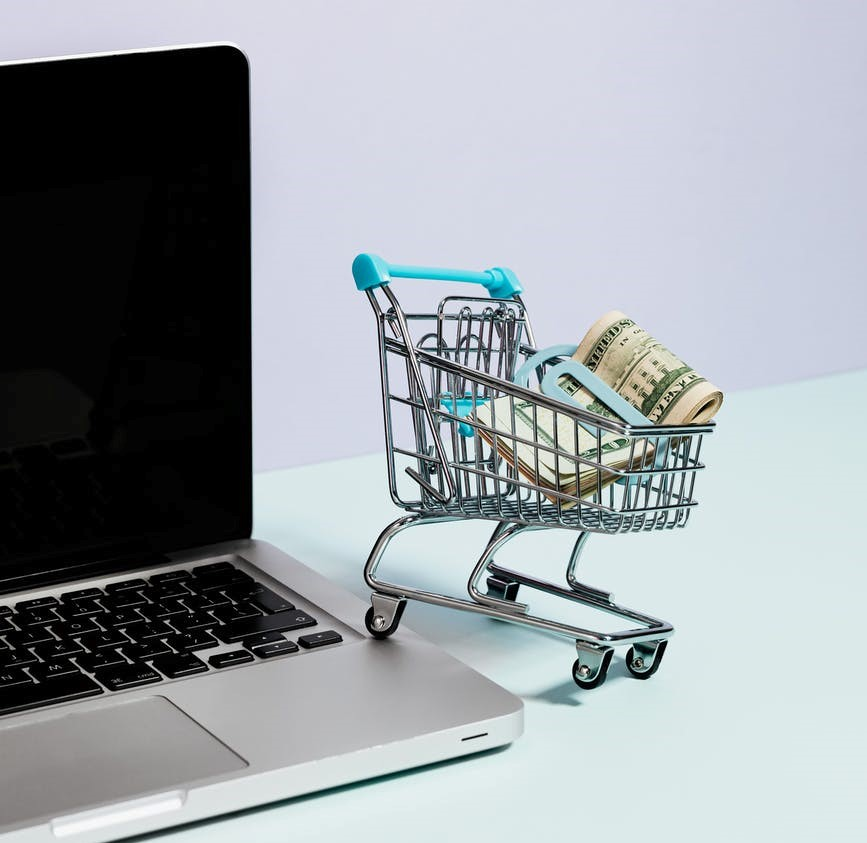 A shopping cart on top of a laptop
