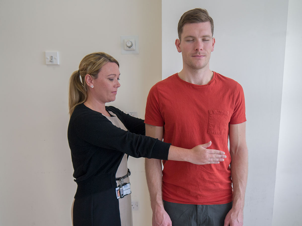 Romberg's test by asking the patient to stand unaided with their eyes closed