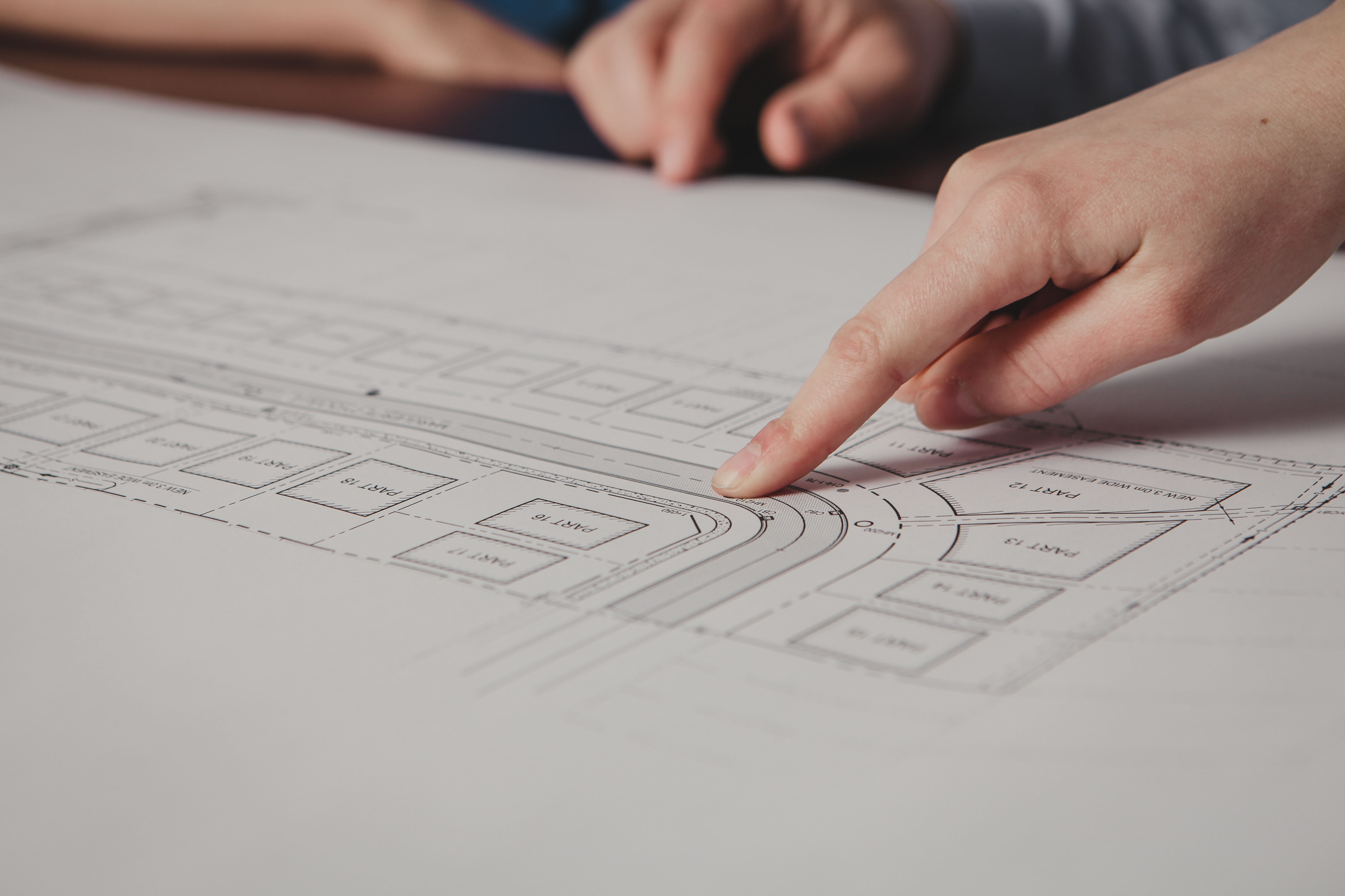 Hand pointing at a section on an engineering plan