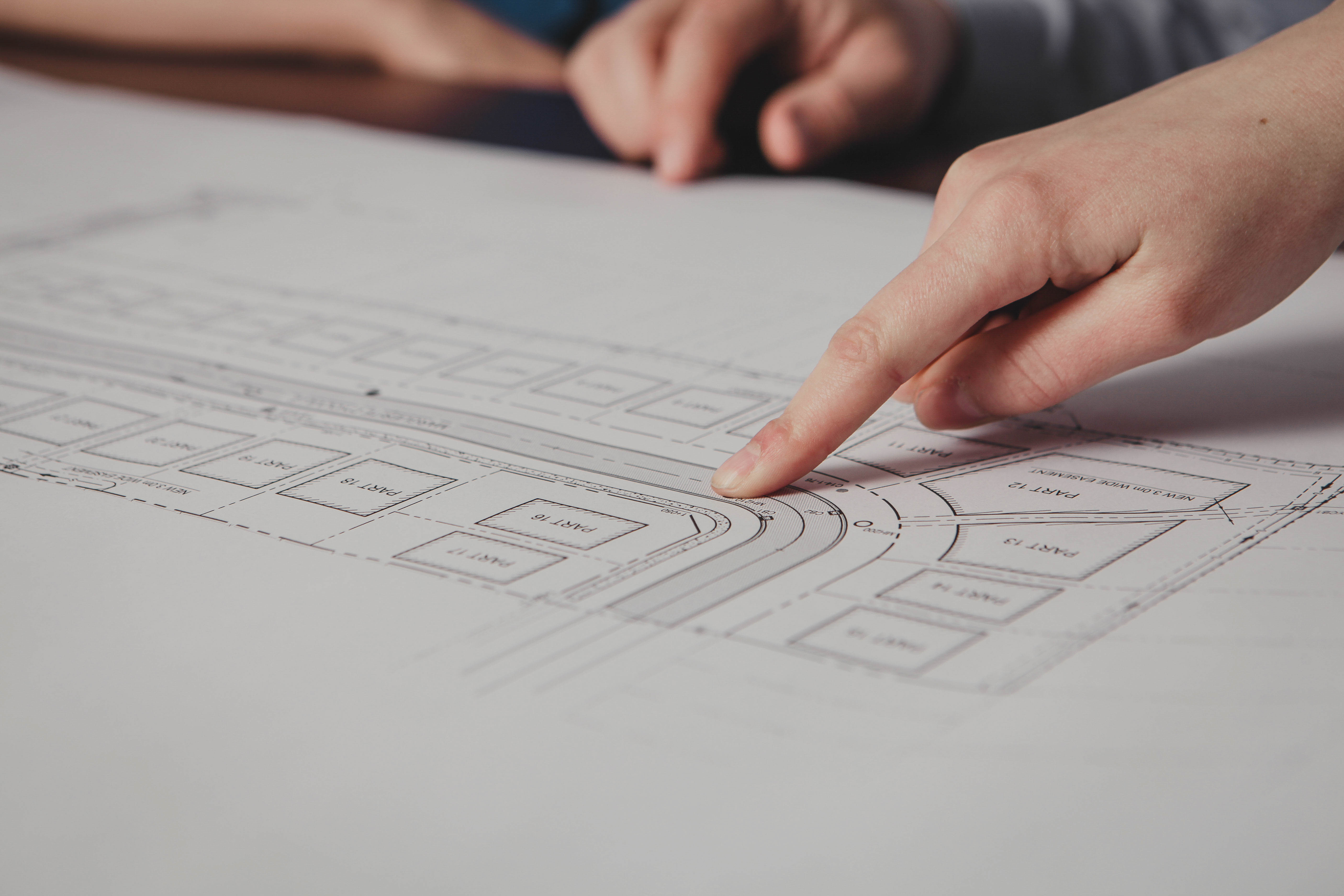 Photo of hand pointing at engineering plans