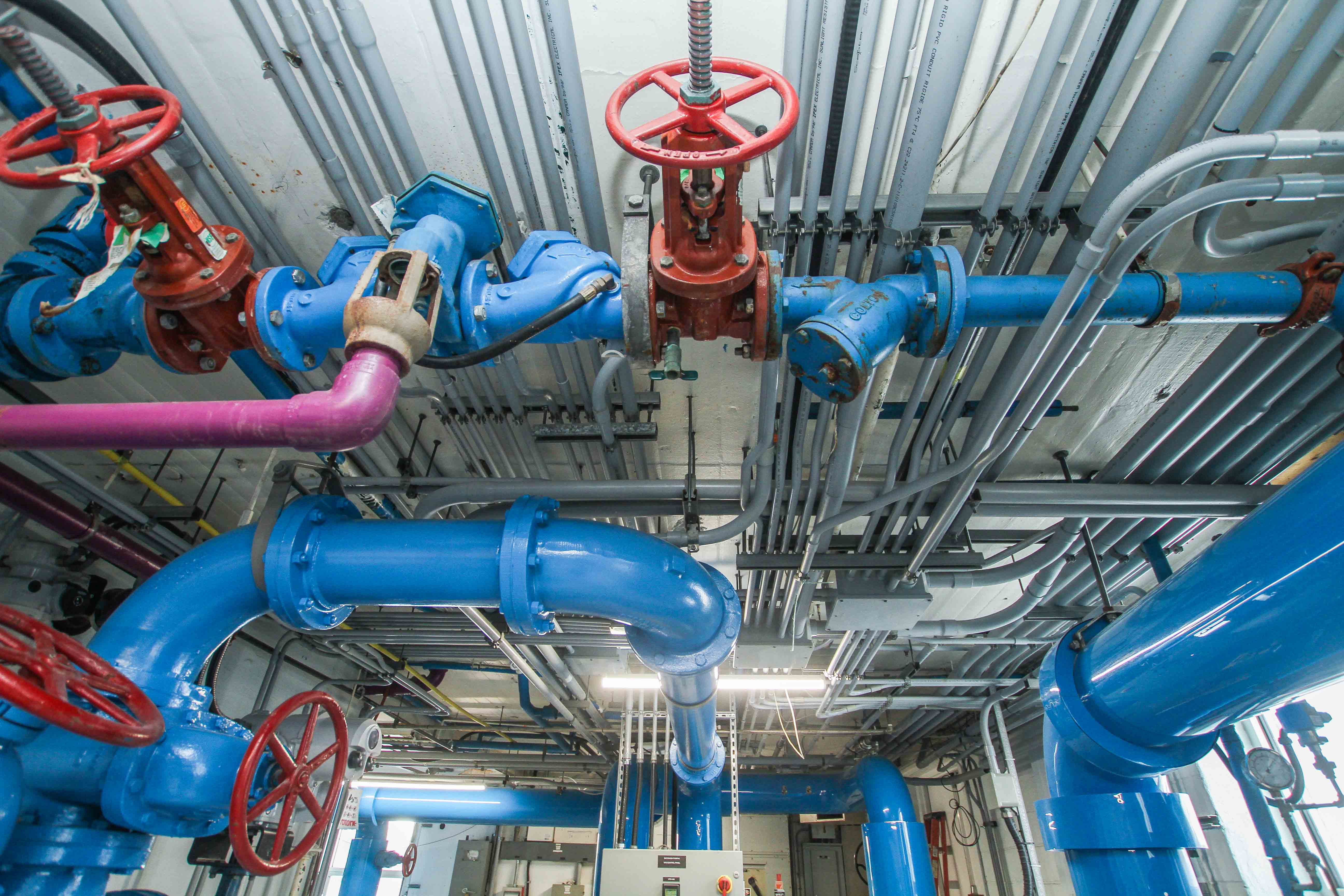 Photo of blue pipes with red valve on ceiling