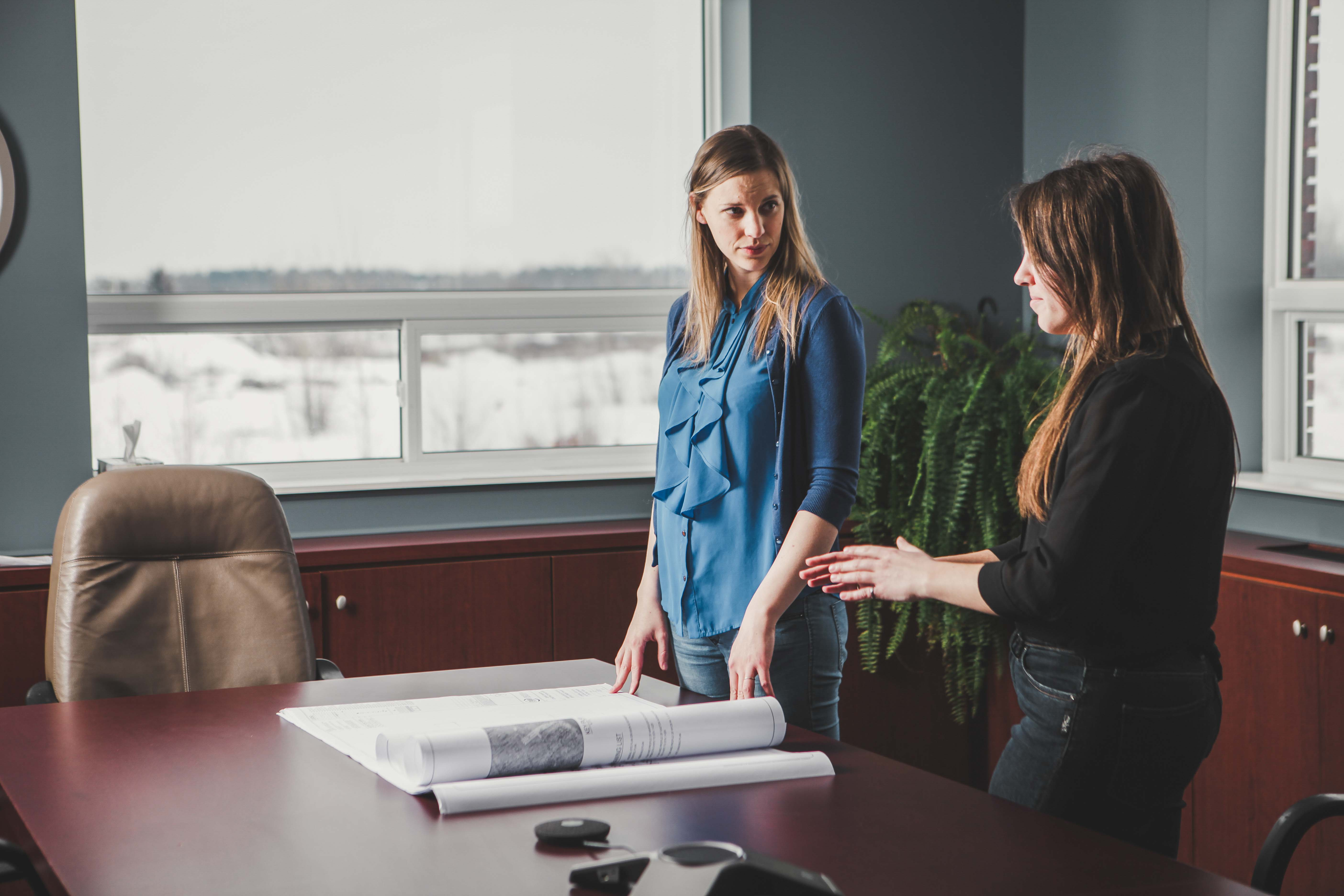 Two women discussing engineering plans