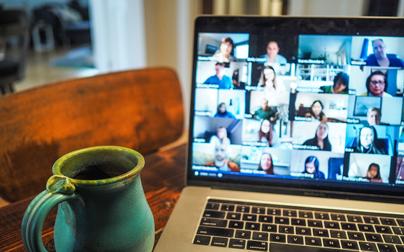 Coffee and laptop showing a group of people on a video call