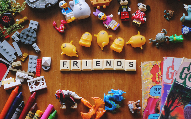 "Various kids items with Scrabble tiles in center of image spelling out the word ""friends"""