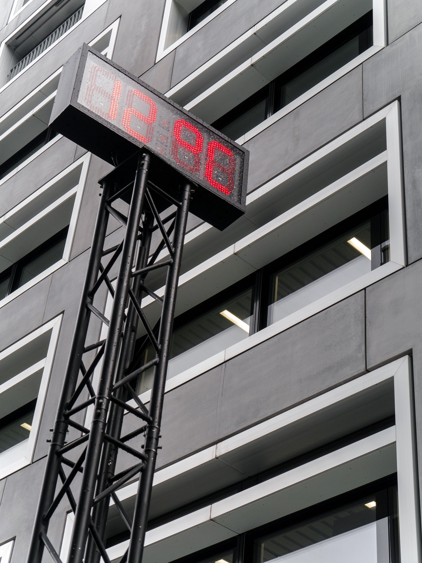Schwarzes Metall und leuchtend rote Schrift verleihen dem Objekt eine Präsenz im Zwischenraum