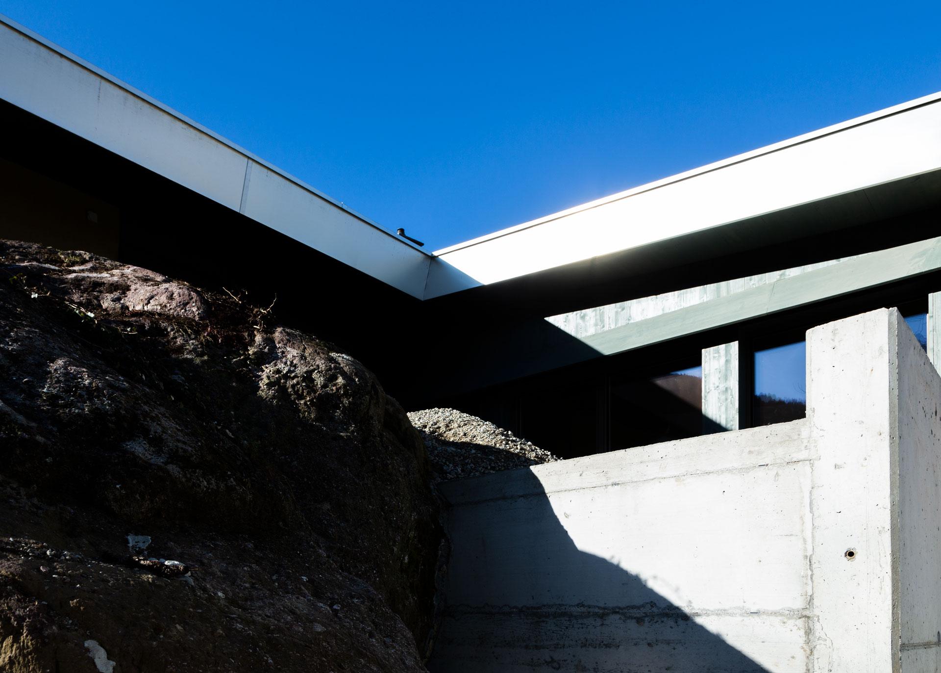Das Leuchtende Aluminiumdach und die rauhen Steinoberflächen bilden starke Kontraste