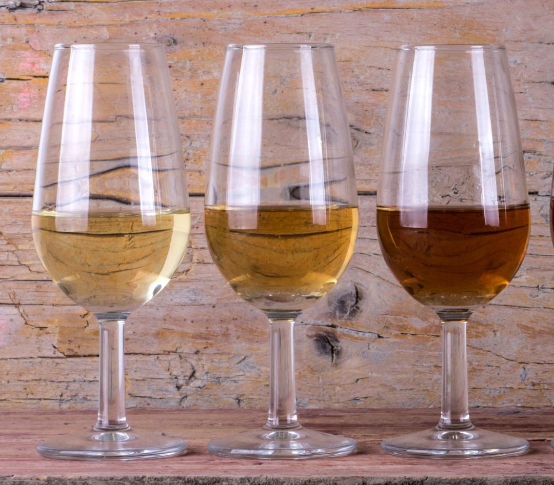 Three glasses of white wine, displaying the darkening colours that result from oxidation.