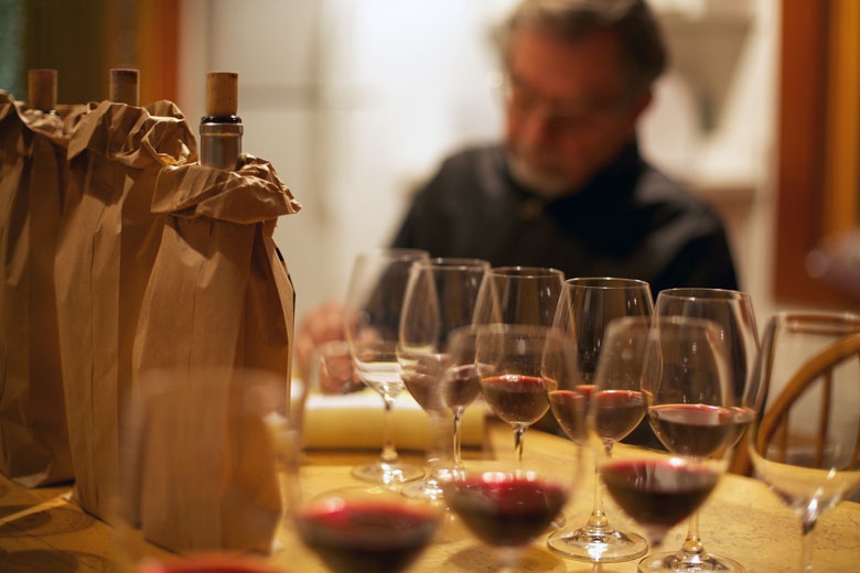 Winemaker conducting blind wine tasting from anonymized bottles.
