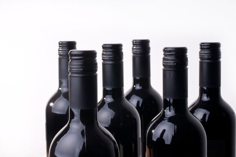 Six light weight unlabeled wine bottles.