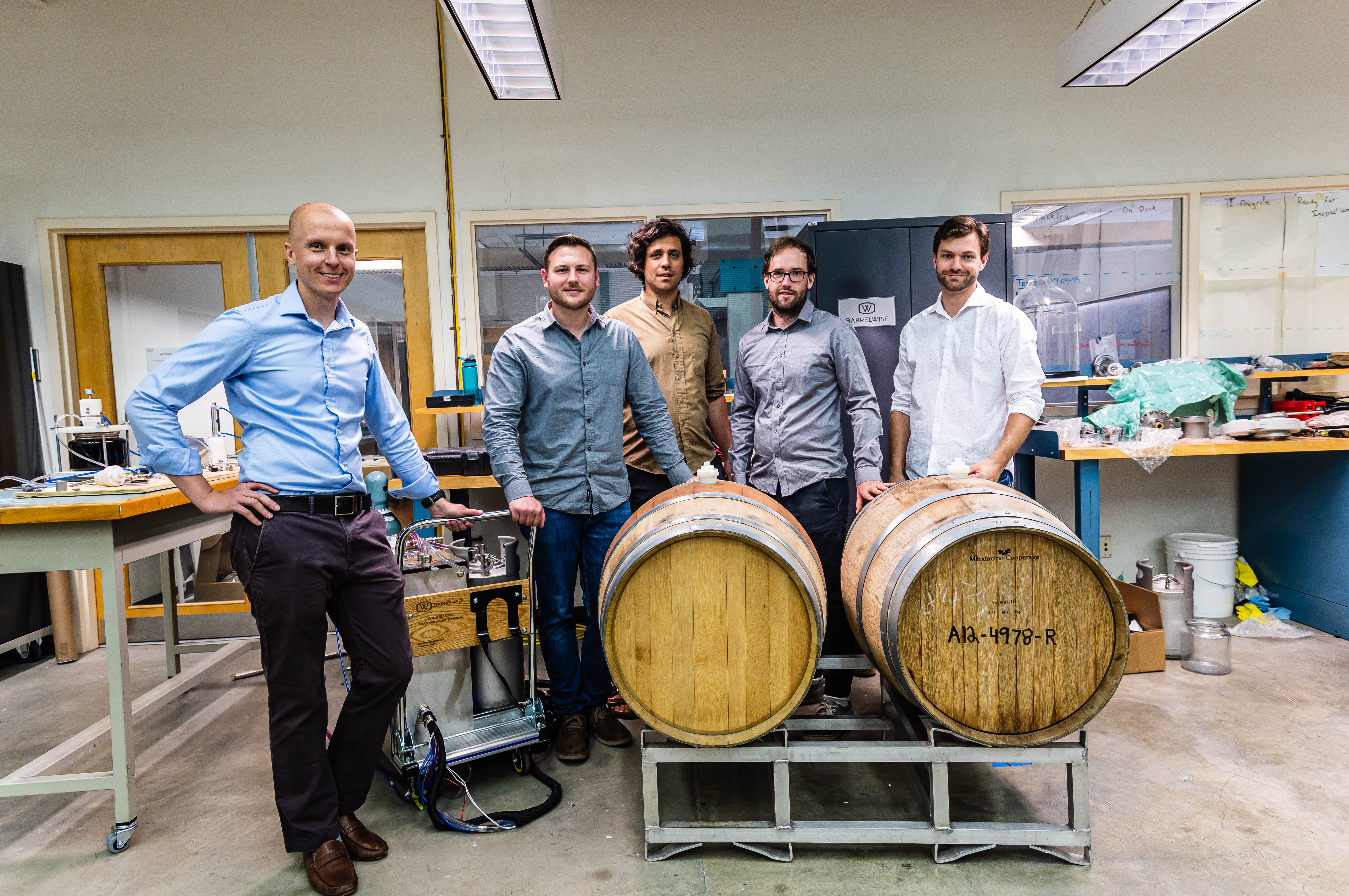 BarrelWise team with an early prototype of the system and two wine barrels