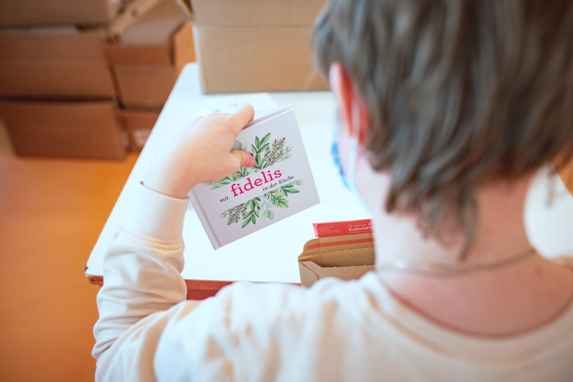 Eine junge Frau mit Behinderung kuvertiert ein Buch.