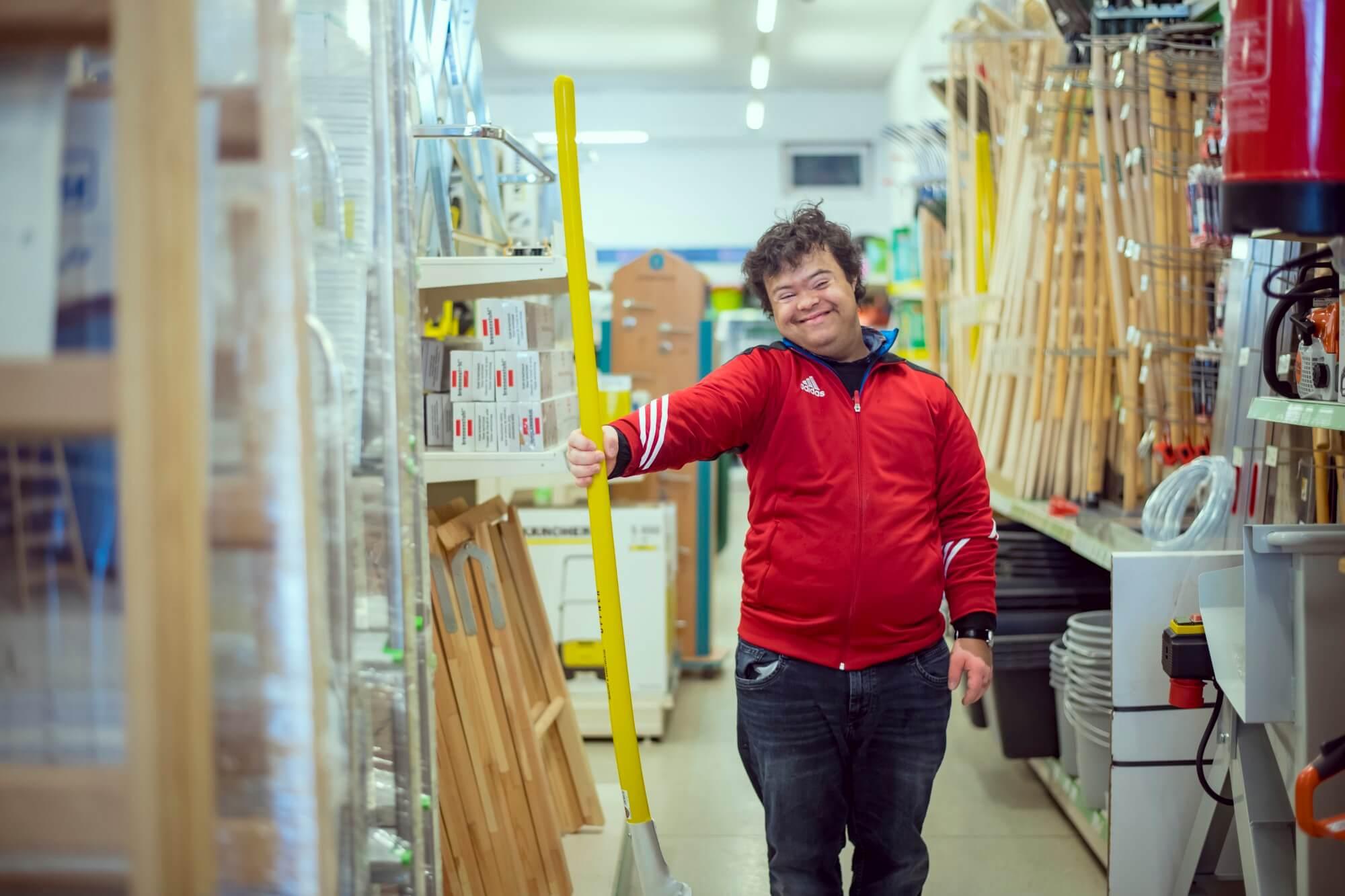 Ein junger Mann mit Behinderung hält eine Schaufel in einem Baumarkt und lächelt.