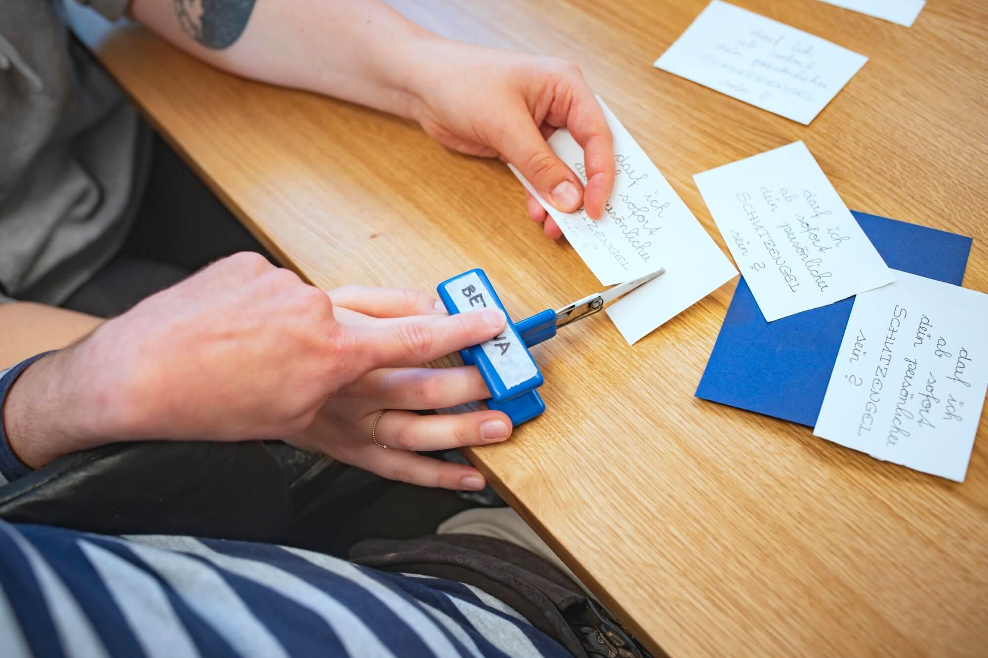 Foto von Händen eines Menschen mit Behinderung, die mit einer speziellen Schere Papier schneiden.