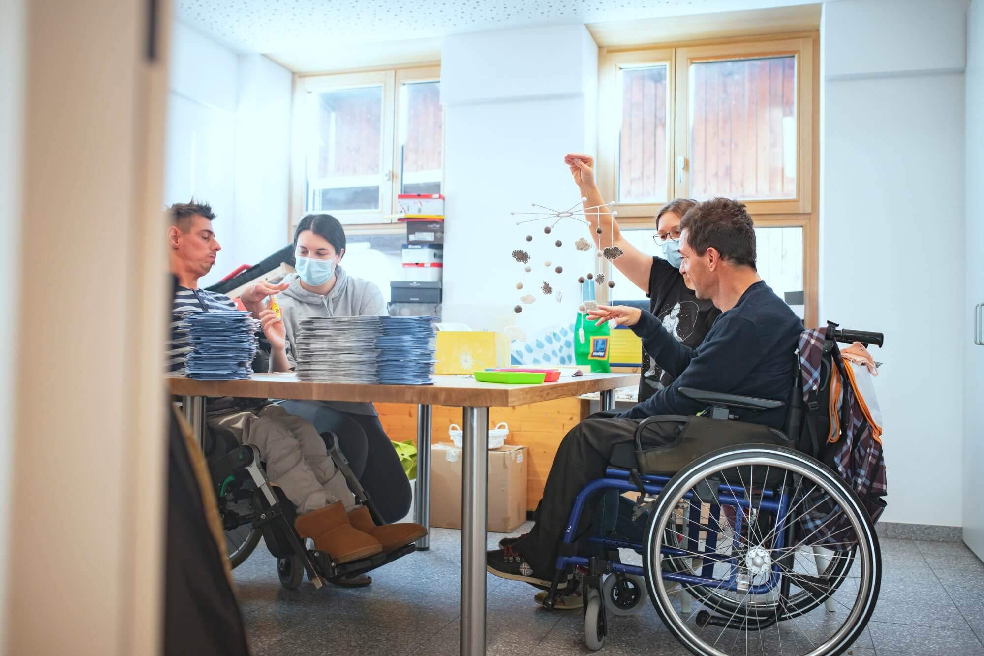 Menschen mit Behinderungen sitzen um einen Tisch und arbeiten mit Papier.