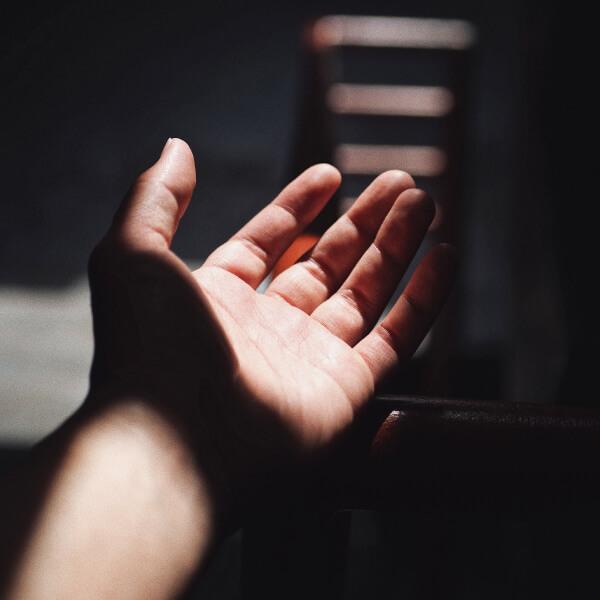 Eine ausgestrecke Hand mit hartem Licht und Schatten