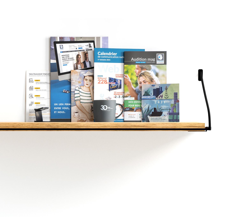 Une étagère avec des imprimés de communications de plusieurs formats
