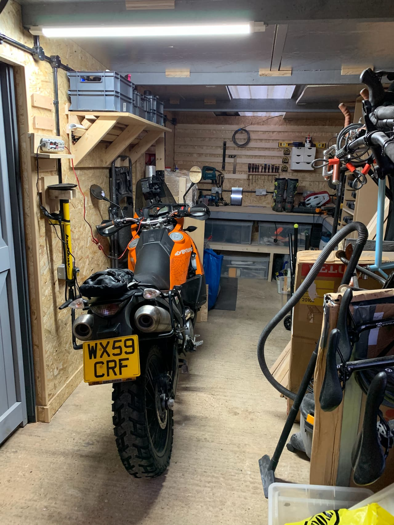 A wood lined garage with motorbike