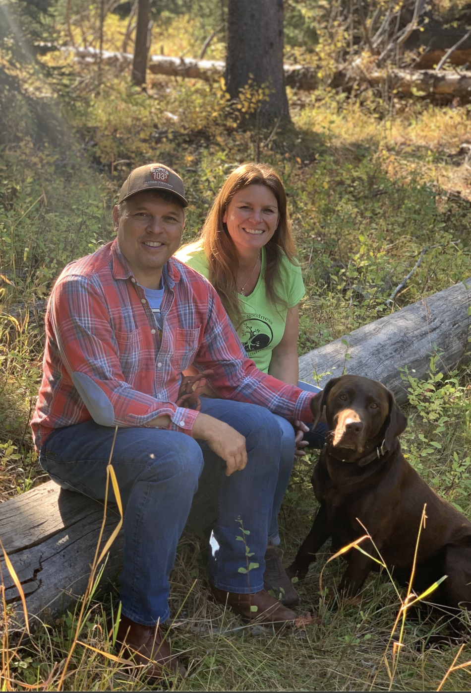 Jay and Kim Bostrom sitting on a log in the woods with their big brown dog