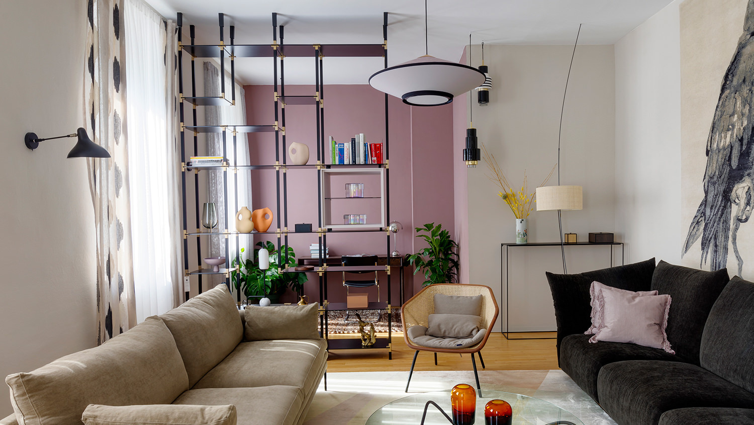 Ein tRACK Regalsystem dient im Wohnzimmer als Raumtrenner und bietet Platz für Bücher und Skulpturen.