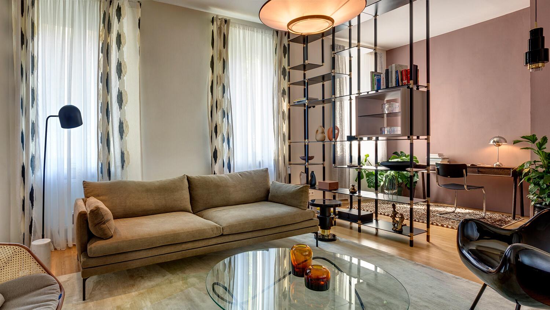 Ein tRACK Regalsystem dient im Wohnzimmer als Raumtrenner zwischen Wohn- und Büro-Bereich.