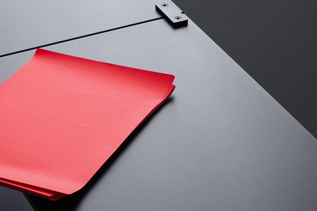 Nahaufnahme eines tRACK Regals auf dem rotes Papier abgelegt ist.