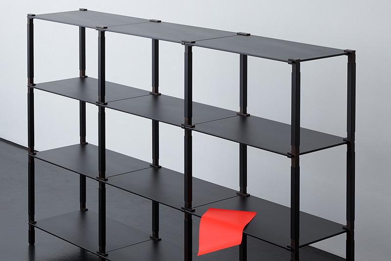 Ein schwarzes tRACK-Regal mit drei Etagen.