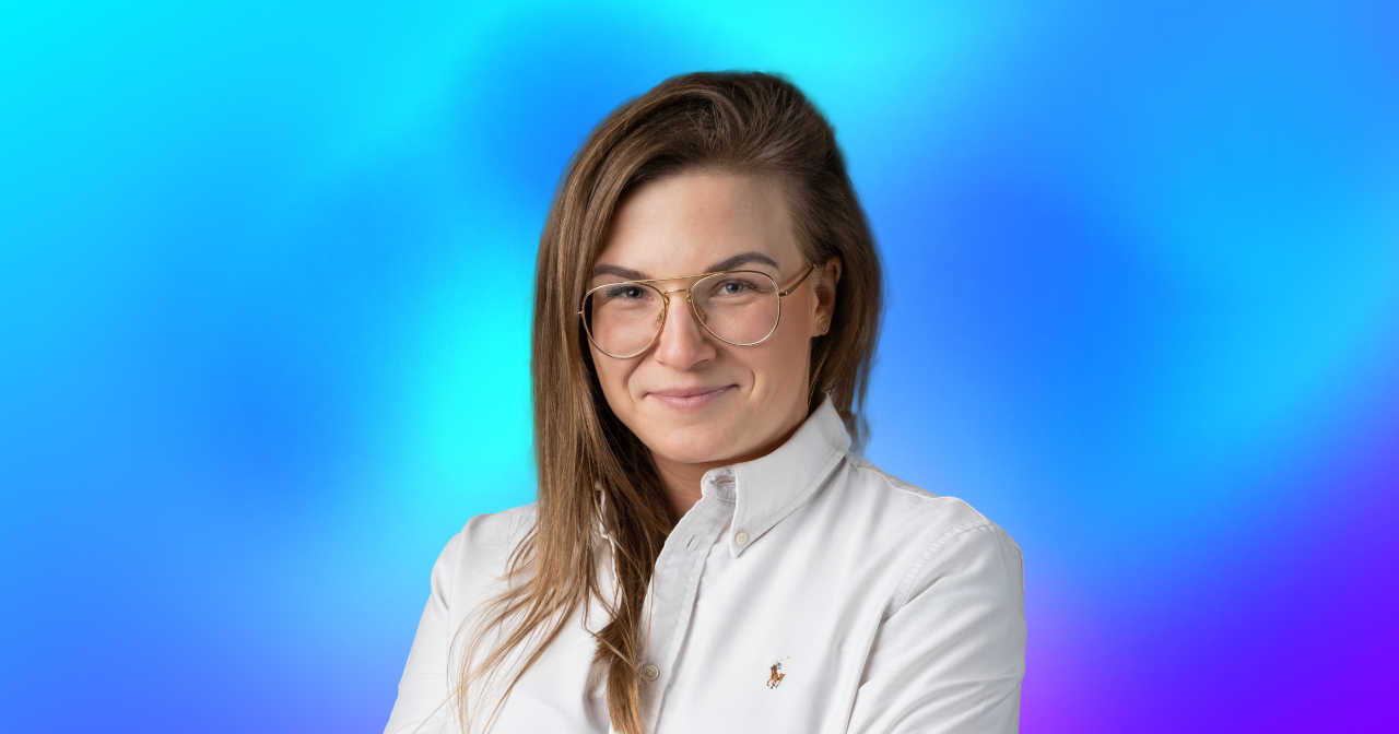 A profile picture of a lady in business attire on a colorful background.