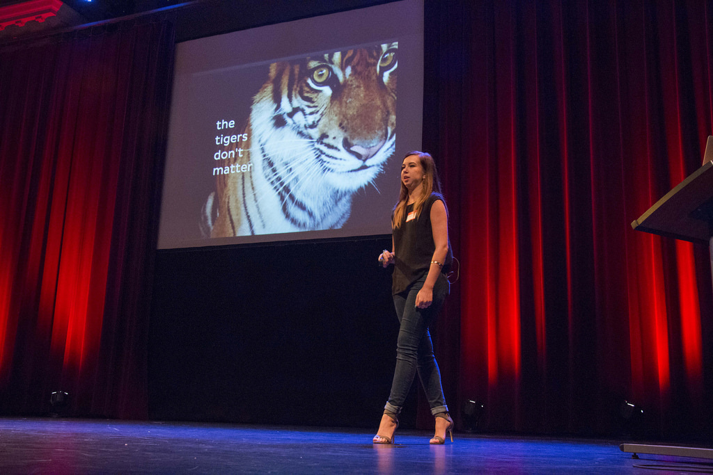 Elyse giving a conference talk on stage with red curtains and a tiger image on the screen.