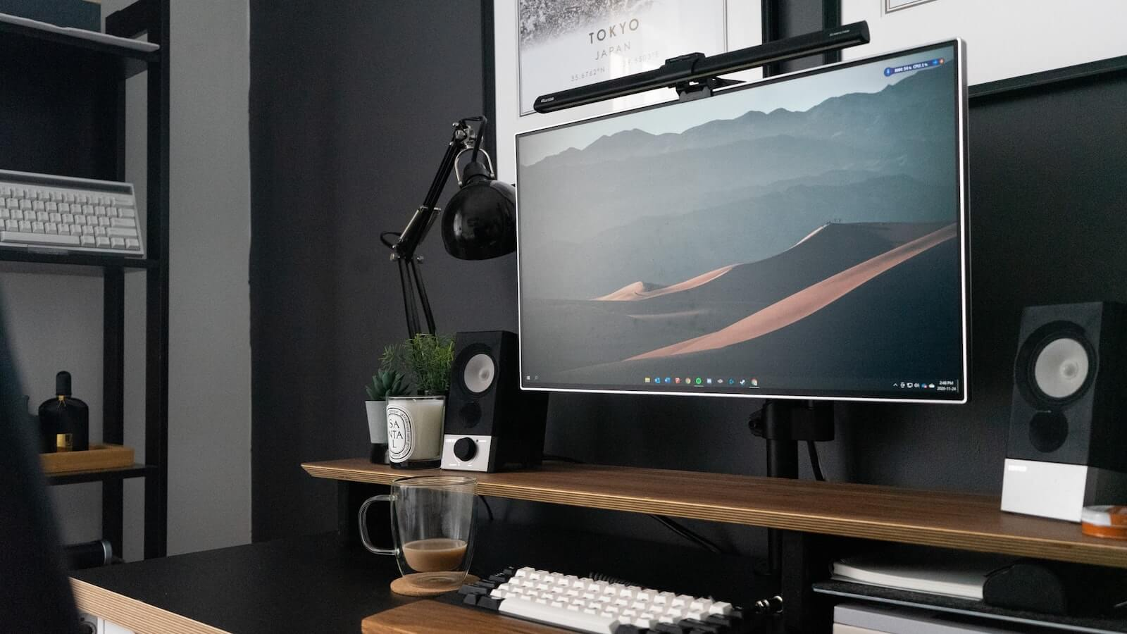 A desk workspace set against a black wall