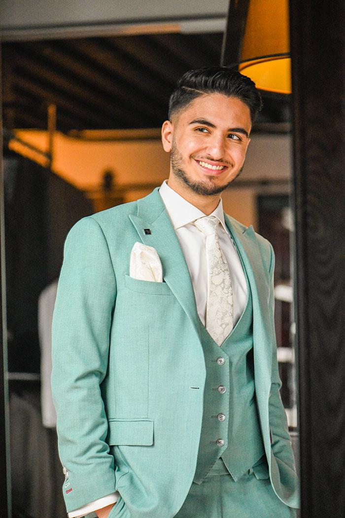 Een man in een licht groene trouwpak gemaakt door Ibrahim.