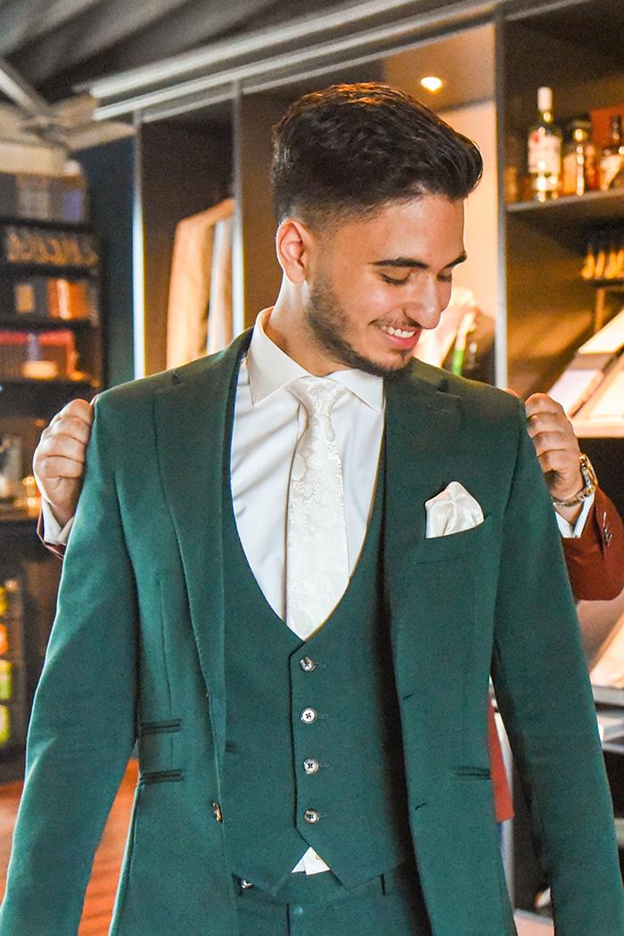 Een man in een donker groene trouwpak gemaakt door Ibrahim.