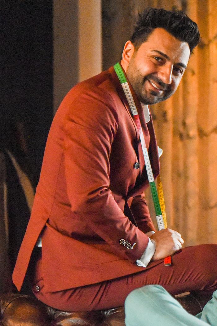 Een man in een rode trouwpak gemaakt door Ibrahim.