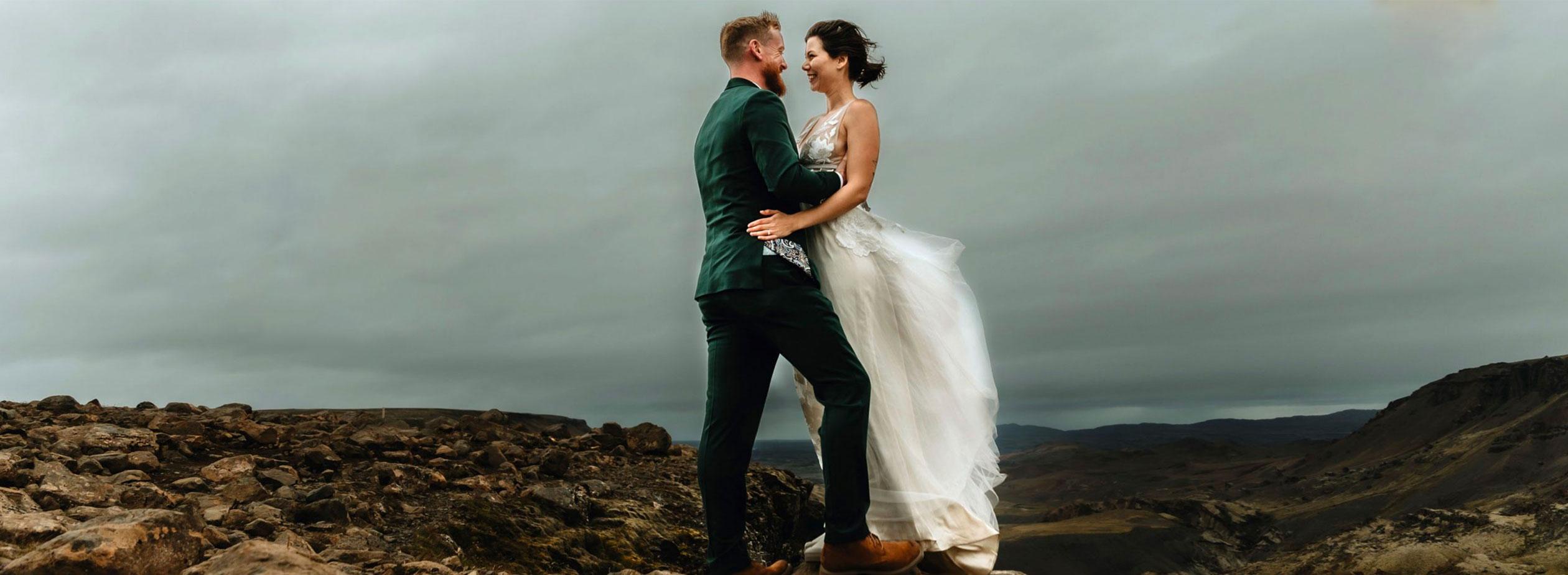Achtergrond afbeelding met een man in pak en een vrouw in een trouwjurk op een rots.