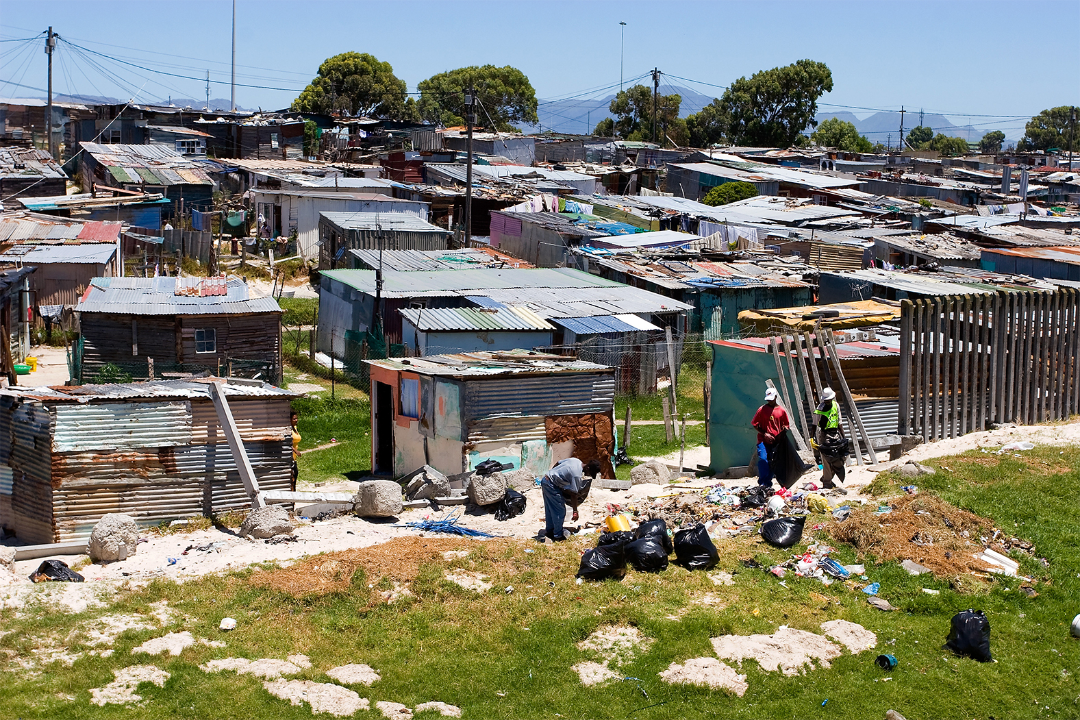 People picking up trash next to makeshift wall of township in Cape Town South Africa