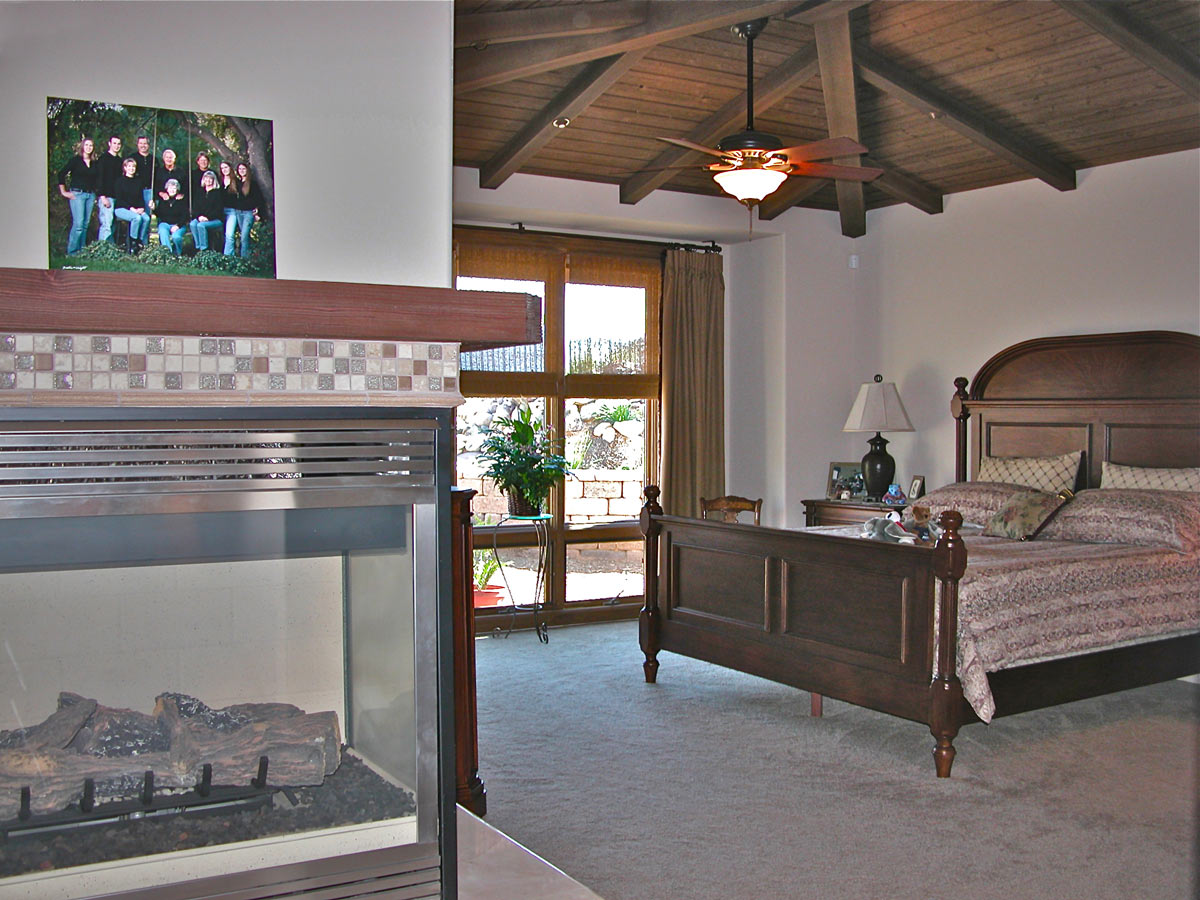 The master bedroom and sitting area connect to a large covered patio with an outdoor fireplace, a nearby spa with waterfall and views to the mountains beyond.