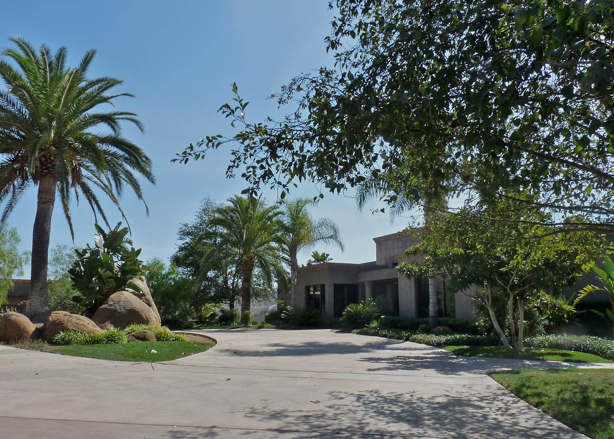 A circular drive leads to the front entrance, while a separate path to the left leads to the five car garage and guest quarters.