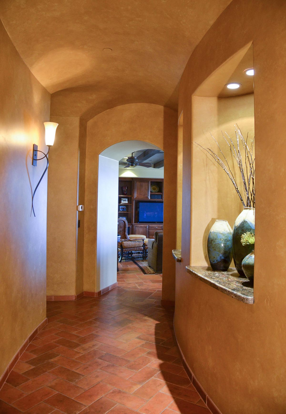 The curving hallway offers views into the music room and art niches, along with access to the powder room, laundry/sewing room and wine cellar.