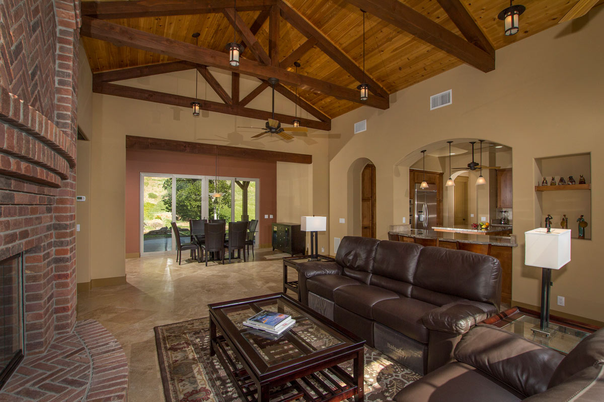 The Great Room boasts heavy timber trusses with cedar tongue and groove, dramatic craftsman lighting, ceiling fans and travertine flooring.