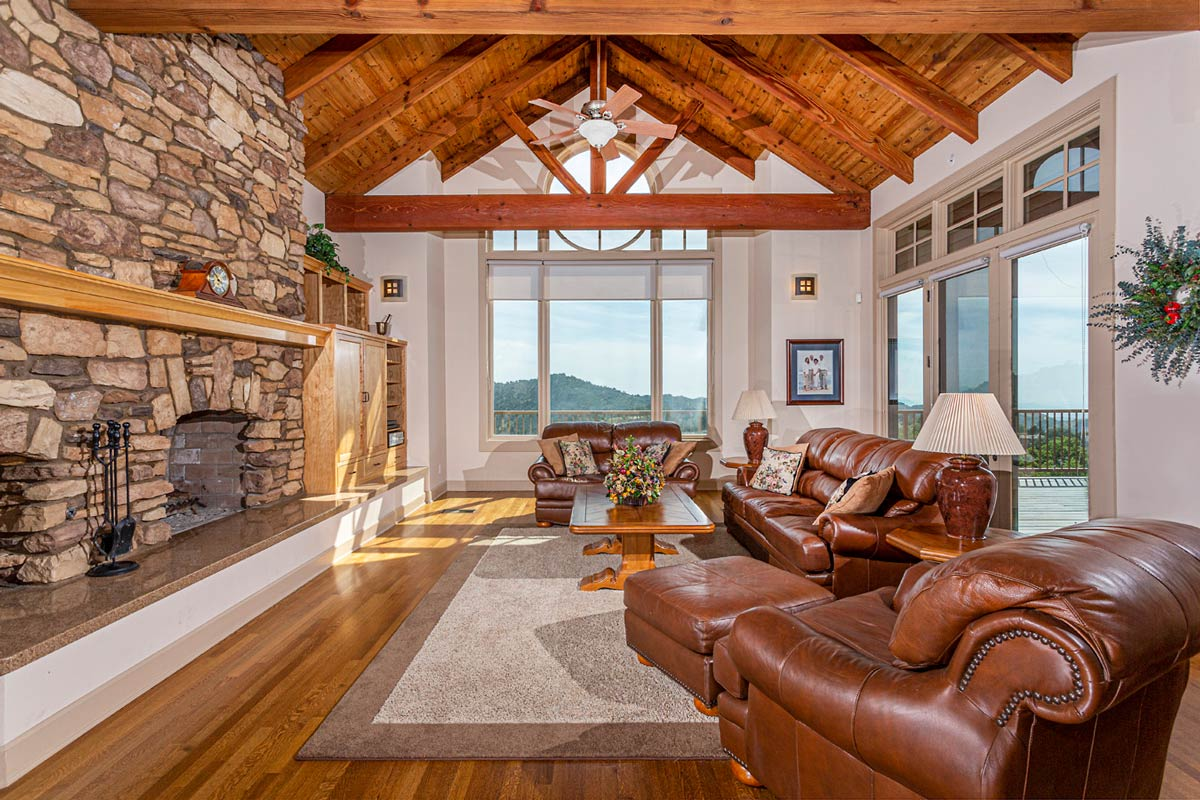 The Great Room has exposed trusses, fireplace with log niche, built-in entertainment center and huge picture windows to the view.
