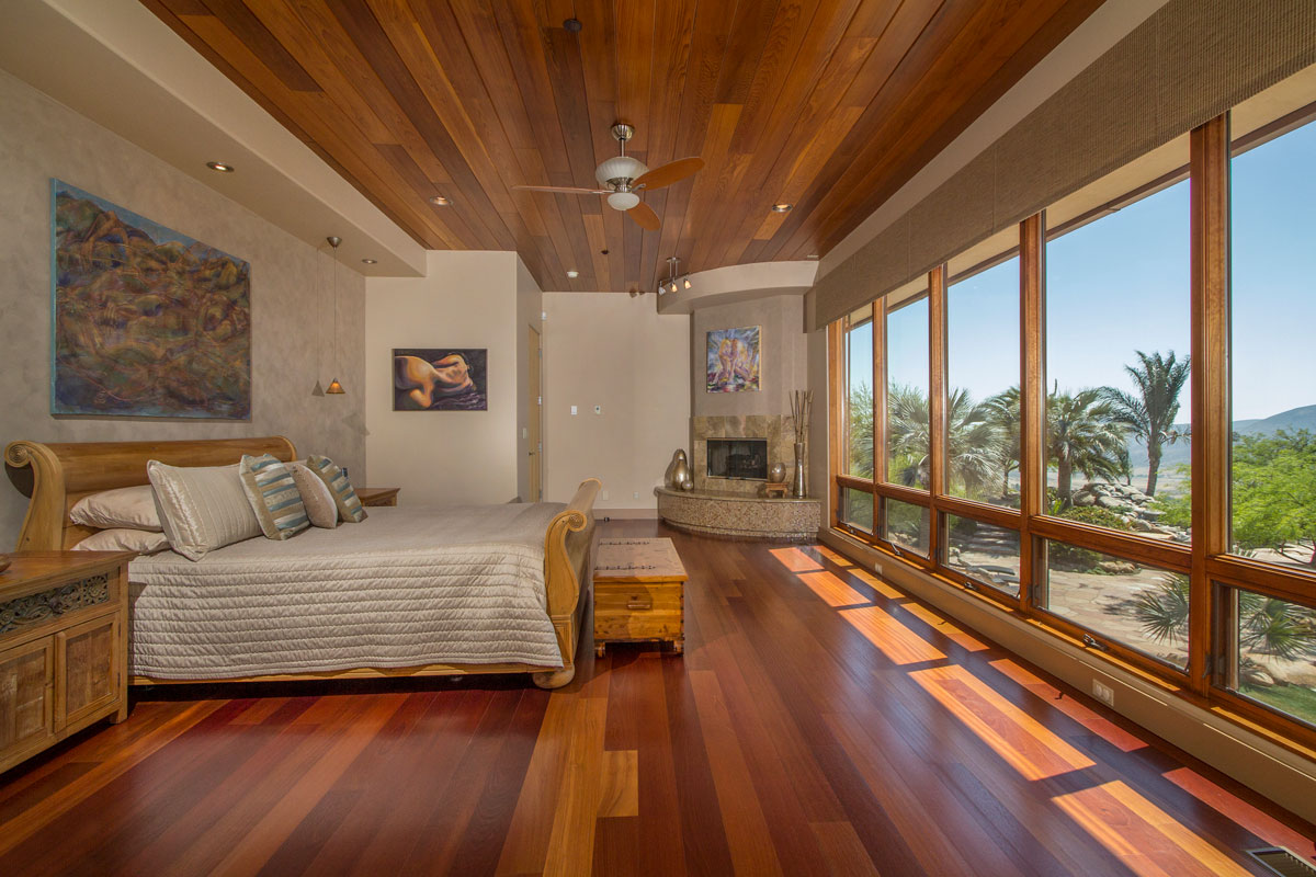 The Master Bedroom has a fireplace and a full wall of glass looking out to the view with remote control solar shades.