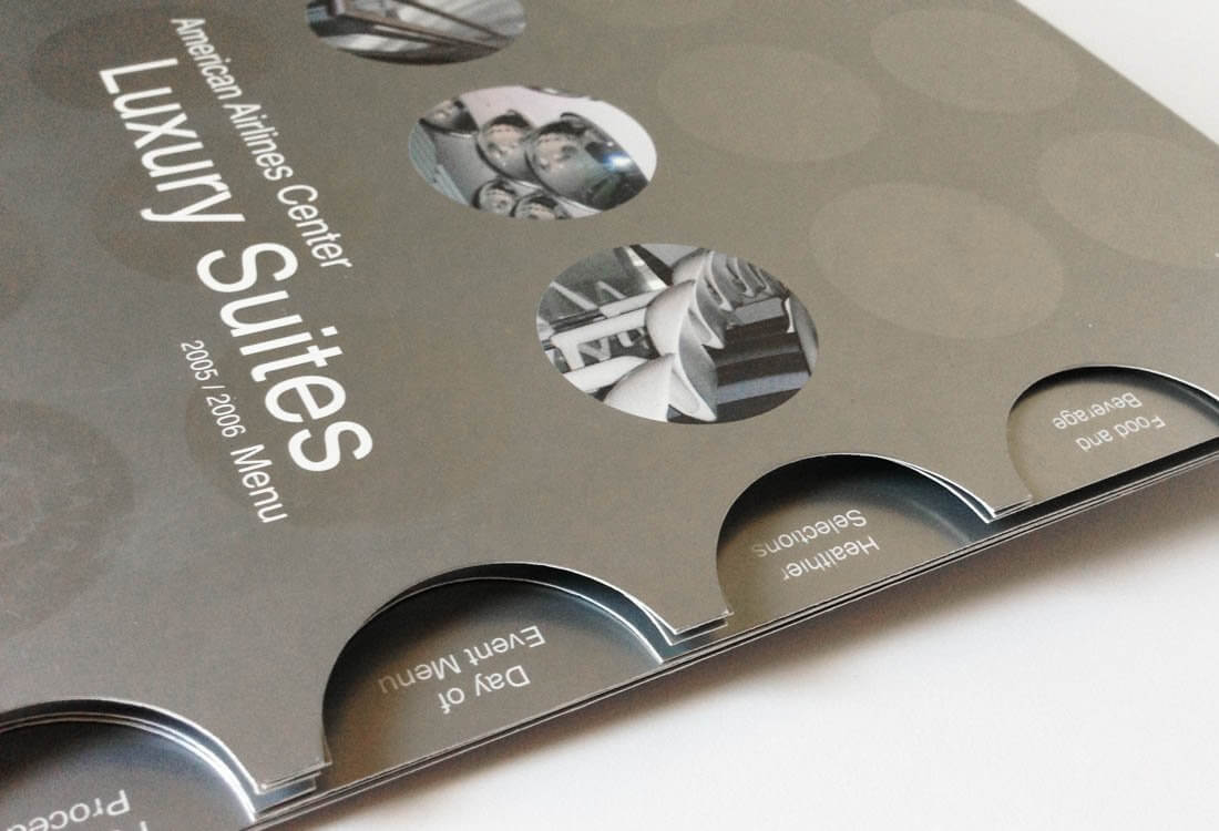 """All bets are off when it comes to the Luxury Suites at the American Airlines Center. The """"Day of the Event"""" menu design features custom die cut elements on the metal menu cover – with cutting-edge graphics for the inside of the menu you can see why people pay a premium for these seats."""