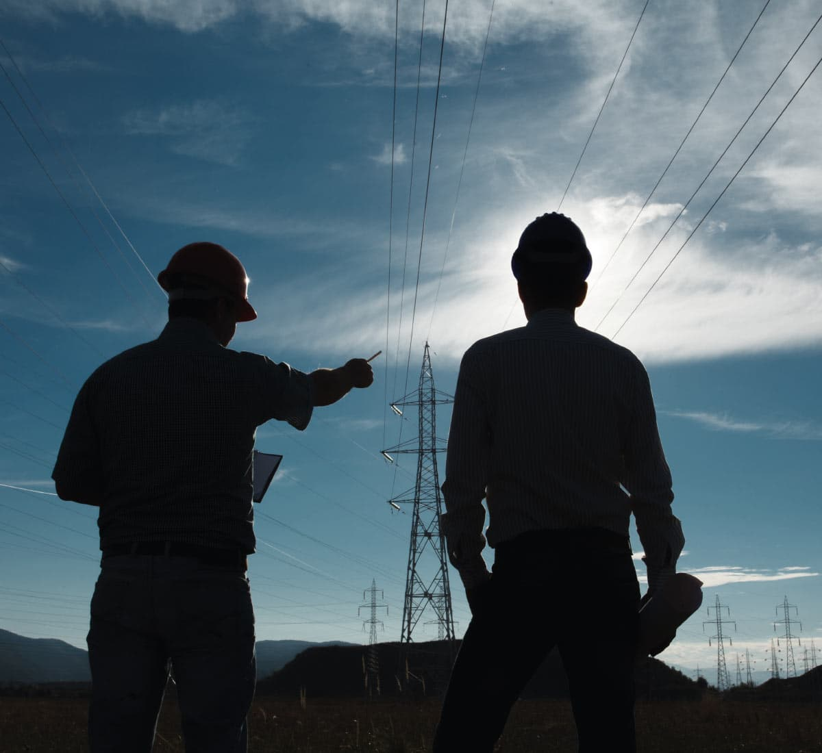 Two builders look at an electric pylon