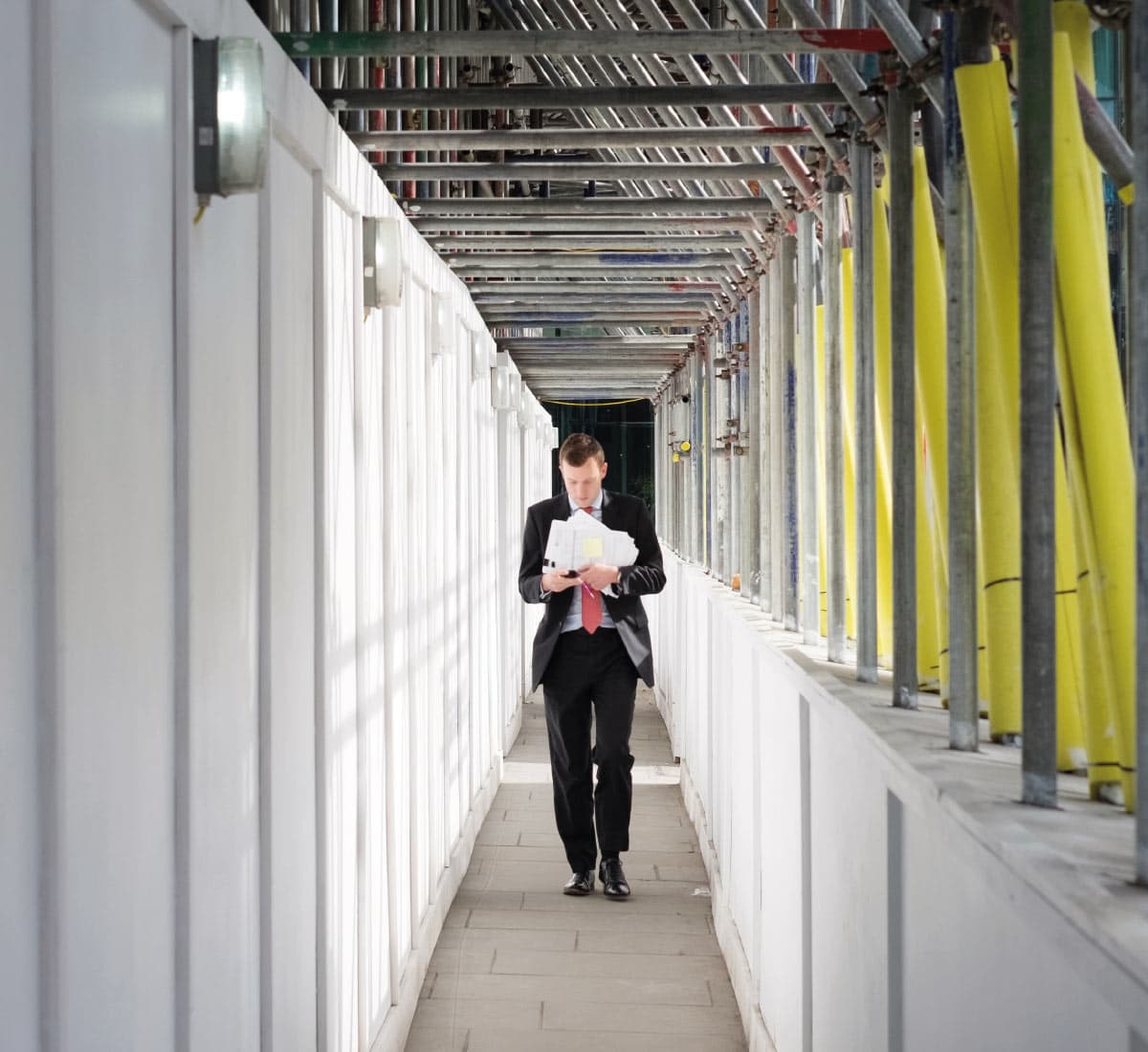 A man wearing a suit walks in a building site