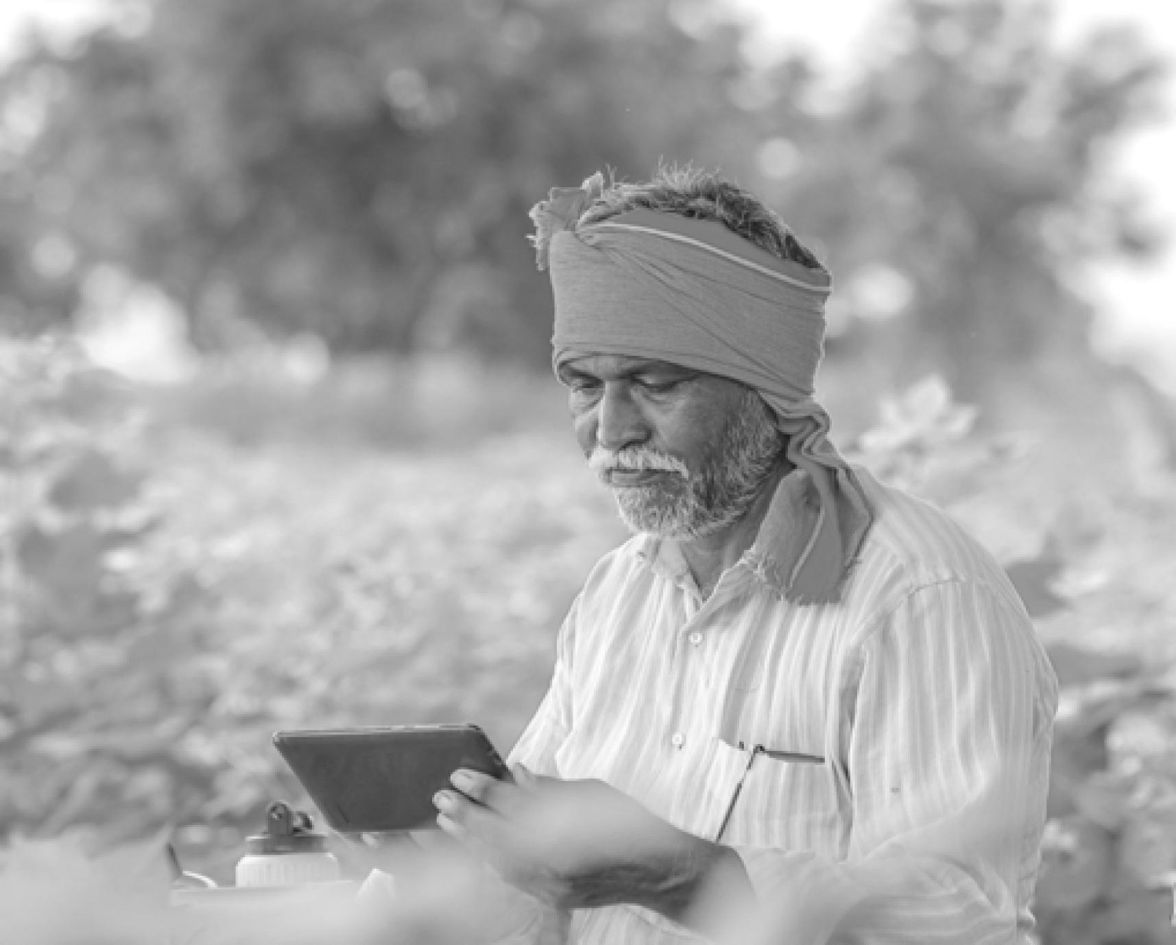 An elderly indian farmer using a phone