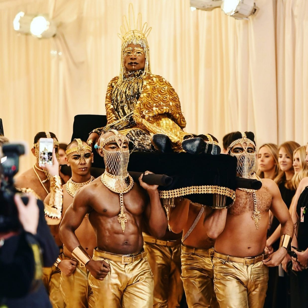 Billy Porter dressed in gold and carried on a litter by six people also in gold.