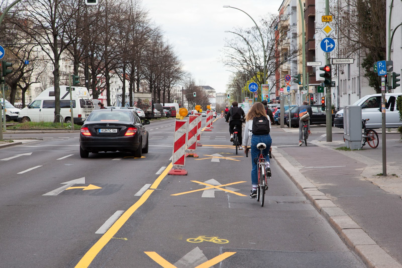 Cyclicts in a pop-up bike lane next to a car.