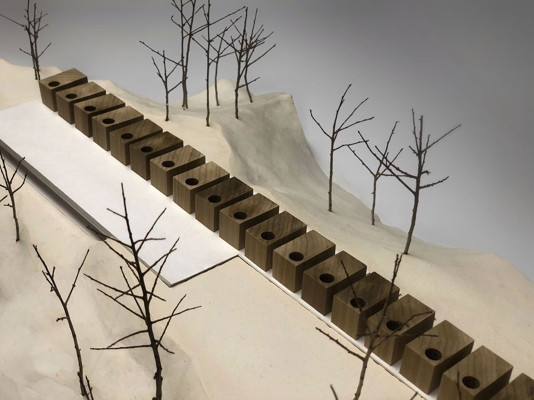 An architectural model with wooden buildings on top of a plaster site.