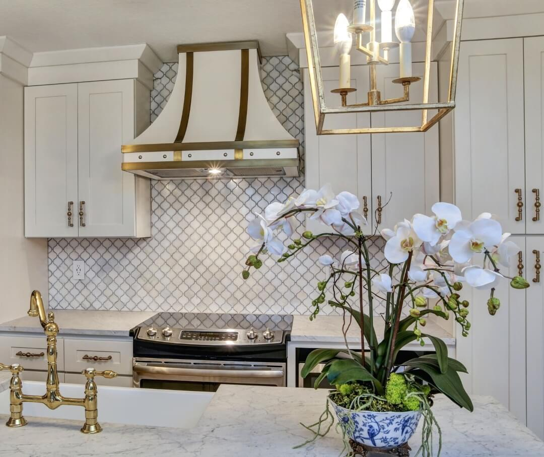 Traditional white custom range hood with gold trim and an orchid